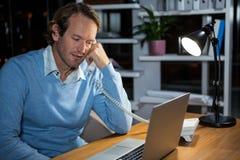 Homme d'affaires parlant au téléphone tout en travaillant dans le bureau Images libres de droits