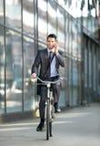 Homme d'affaires parlant avec le téléphone portable et montant une bicyclette images libres de droits