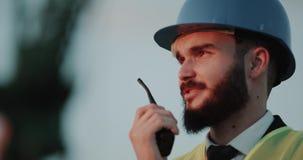 Homme d'affaires parlant de plan rapproché utilisant une radio et porter un casque de sécurité banque de vidéos