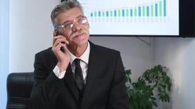 Homme d'affaires parlant du téléphone dans le bureau devant le bureau Images libres de droits