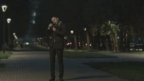 Homme d'affaires parlant par le téléphone tout en marchant en parc clips vidéos