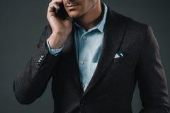Homme d'affaires parlant sur le smartphone d'isolement sur le gris images libres de droits