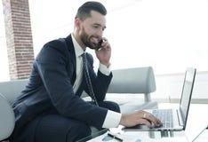 Homme d'affaires parlant sur le smartphone et le texte de dactylographie sur l'ordinateur portable Images libres de droits