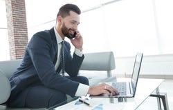 Homme d'affaires parlant sur le smartphone et le texte de dactylographie sur l'ordinateur portable Photographie stock libre de droits