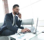 Homme d'affaires parlant sur le smartphone et le texte de dactylographie sur l'ordinateur portable Photos libres de droits