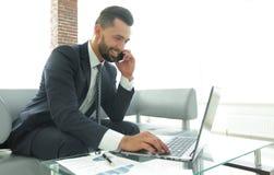 Homme d'affaires parlant sur le smartphone et le texte de dactylographie sur l'ordinateur portable Photographie stock