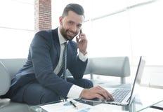 Homme d'affaires parlant sur le smartphone et le texte de dactylographie sur l'ordinateur portable Images stock