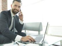 Homme d'affaires parlant sur le smartphone et le texte de dactylographie sur l'ordinateur portable Photo stock