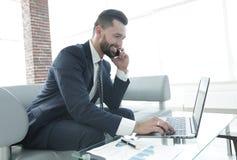 Homme d'affaires parlant sur le smartphone et le texte de dactylographie sur l'ordinateur portable Image stock