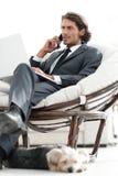 Homme d'affaires parlant sur le smartphone se reposant dans la chaise dans sa maison Images libres de droits