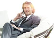 Homme d'affaires parlant sur le smartphone se reposant dans la chaise dans sa maison Image libre de droits