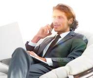 Homme d'affaires parlant sur le smartphone se reposant dans la chaise dans sa maison Photographie stock libre de droits