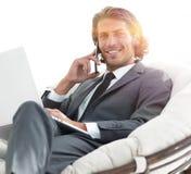 Homme d'affaires parlant sur le smartphone se reposant dans la chaise dans sa maison Photographie stock