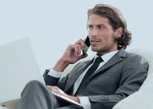 Homme d'affaires parlant sur le smartphone se reposant dans la chaise dans sa maison Images stock