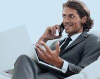 Homme d'affaires parlant sur le smartphone se reposant dans la chaise dans sa maison Image stock