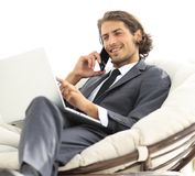 Homme d'affaires parlant sur le smartphone se reposant dans la chaise dans sa maison Photos libres de droits