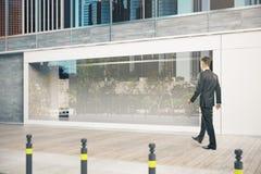 Homme d'affaires passant la devanture Photographie stock