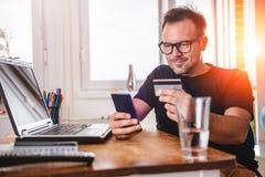 Homme d'affaires payant avec la carte de crédit au téléphone intelligent Images stock