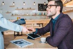 Homme d'affaires payant avec la carte de crédit en café Photo libre de droits