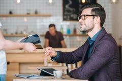 Homme d'affaires payant avec la carte de crédit en café Images stock
