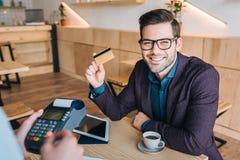 Homme d'affaires payant avec la carte de crédit en café Photos libres de droits