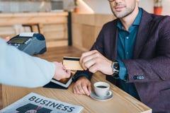 Homme d'affaires payant avec la carte de crédit en café Photo stock