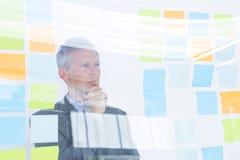 Homme d'affaires perplexe regardant des post-its sur le mur Images stock