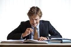 Homme d'affaires perplexe travaillant sur le problème Photographie stock libre de droits