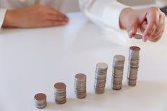 Homme d'affaires plaçant la pièce de monnaie au-dessus de la pile croissante de pièces de monnaie image stock