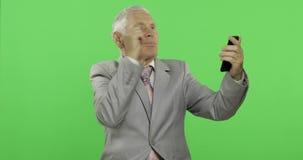 Homme d'affaires plus âgé bel ayant la causerie visuelle utilisant le smartphone Plan rapproch? banque de vidéos