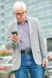 Homme d'affaires plus âgé utilisant le smartphone sur la rue image libre de droits