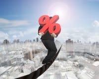 Homme d'affaires portant le signe de pourcentage 3D rouge équilibrant sur le fil Photos stock