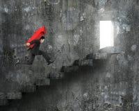 Homme d'affaires portant le signe rouge de flèche fonctionnant sur des escaliers avec la porte Images stock
