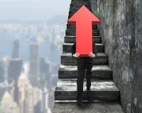 Homme d'affaires portant le signe rouge de flèche s'élevant sur des escaliers Photographie stock