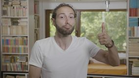 Homme d'affaires portant les vêtements sport faisant des pouces renonçant à la réaction positive et montrant l'appui et l'approba banque de vidéos