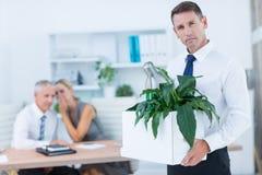 Homme d'affaires portant ses affaires avec des collègues derrière Image libre de droits
