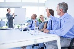 Homme d'affaires posant la question au cours de la réunion photographie stock