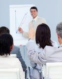 Homme d'affaires posant une question à une présentation Photos stock