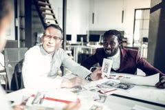 Homme d'affaires poss?dant la revue de mode parlant ? ses employ?s photographie stock