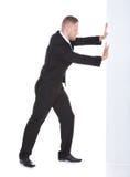 Homme d'affaires poussant le bord d'un signe blanc vide Photographie stock libre de droits