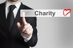 Homme d'affaires poussant le coeur plat de charité de bouton Photographie stock libre de droits