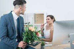 Homme d'affaires présent le bouquet des roses à son collègue sur le lieu de travail Images stock