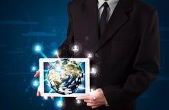 Homme d'affaires présent le globe de la terre 3d dans le comprimé Photo stock