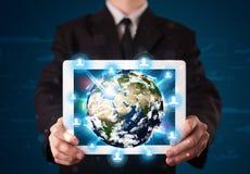 Homme d'affaires présent le globe de la terre 3d dans le comprimé Images libres de droits