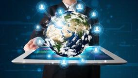 Homme d'affaires présent le globe de la terre 3d dans le comprimé Photo libre de droits