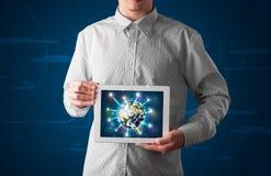 Homme d'affaires présent le globe de la terre 3d dans le comprimé Photographie stock