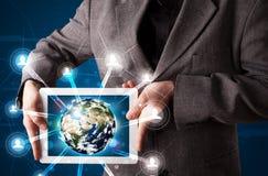 Homme d'affaires présent le globe de la terre 3d dans le comprimé Photographie stock libre de droits