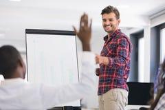 Homme d'affaires présentant un exposé à ses collègues au travail Photos stock