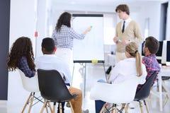 Homme d'affaires présentant un exposé à ses collègues au travail se tenant devant un flipchart Photo libre de droits