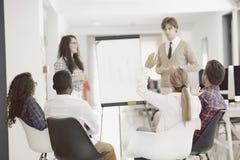 Homme d'affaires présentant un exposé à ses collègues au travail se tenant devant un flipchart Photographie stock